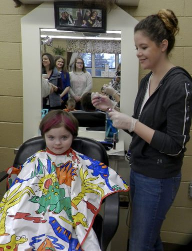 Ayla Strauss, 5, of Edinburg, gets pink hair by Triplett Tech cosmetology student Jayden Austin, 18.  Kaley Toy/Daily